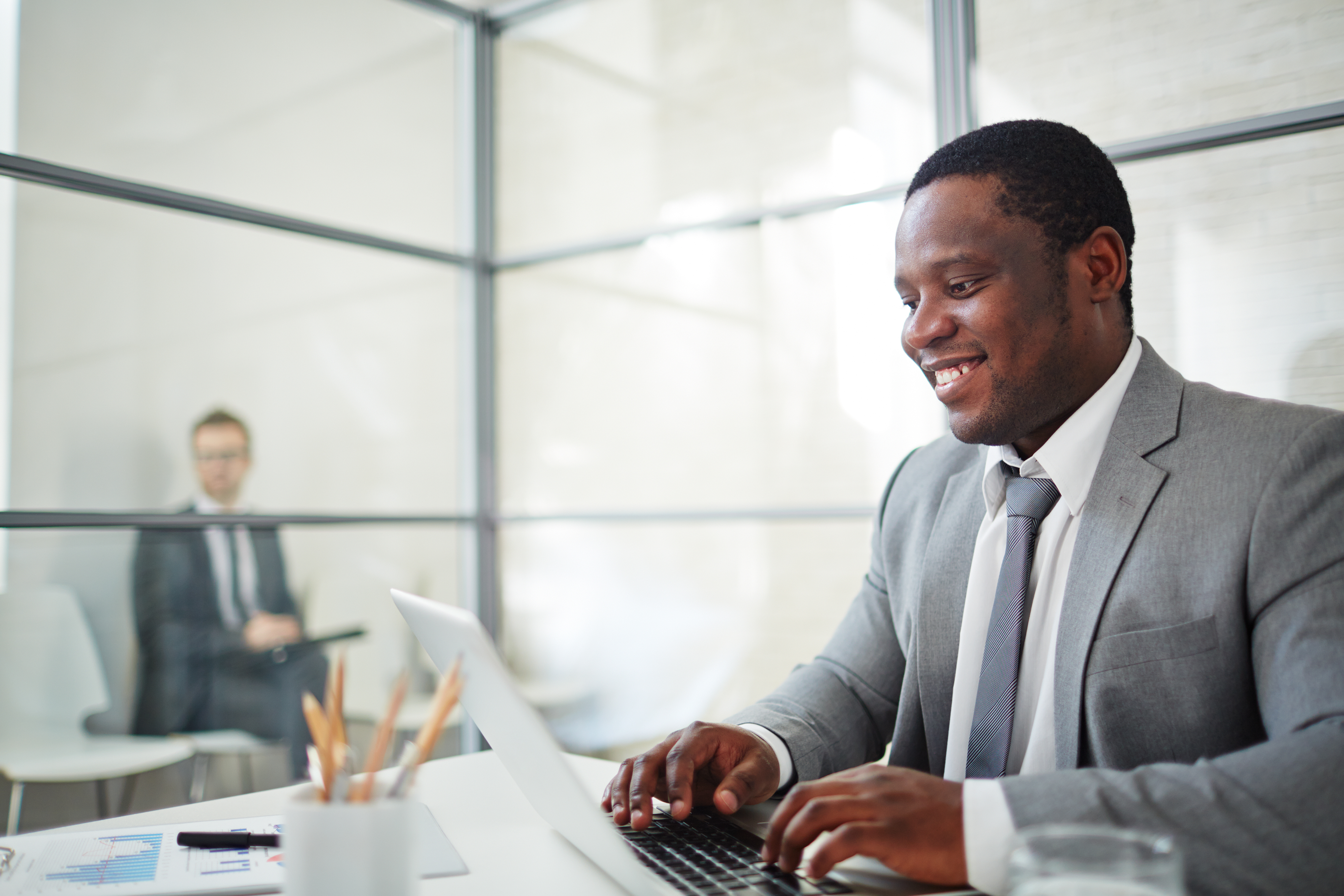 African businessman in formalwear typing on laptop